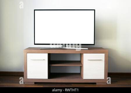 Big flat LCD Television with a blank screen on a wooden tv stand - Stock Photo