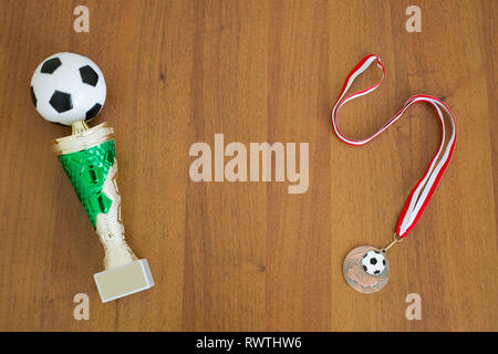 Football trophy and medal on a wooden background Stock Photo