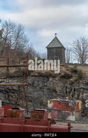 A small Norwegian Chapel overlooks a Shipyard and Industrial Setting in Maloy in Norway on a cold winters morning. - Stock Photo