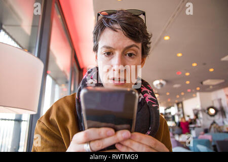 Beautiful young woman in warm clothes sitting in cafe and checking her smartphone, surprised and confused, blurred background, head and shoulders