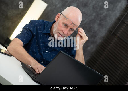 a senior businessman using laptop, he is having difficulties and vision problems - Stock Photo