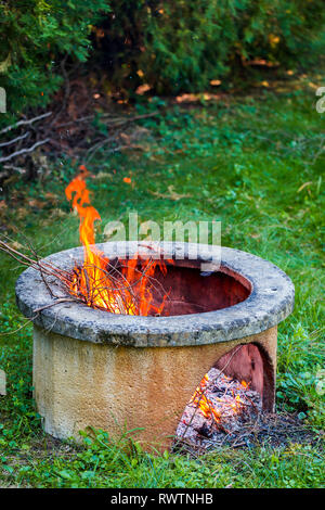 Dry branches burn in isolated campfire pit in the garden. High bright flames flickering on open garden fire pit. Vertical photo - Stock Photo