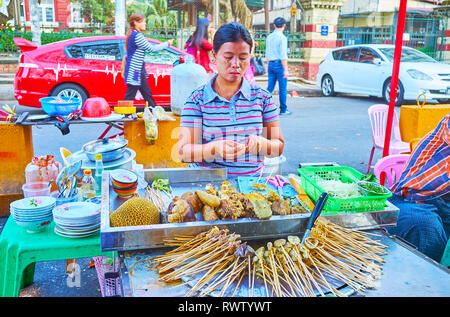 YANGON, MYANMAR - FEBRUARY 15, 2018: The vendor of the street food stall cooks the pork offal on skewers, on February 15 in Yangon. - Stock Photo