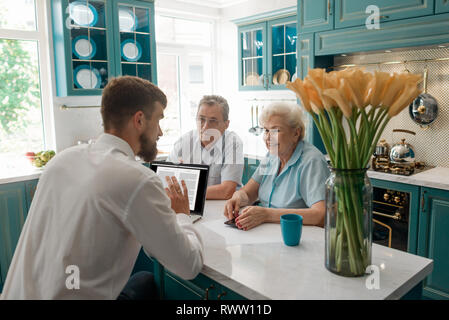 Financial advisor talks with elderly clients in their home. Cozy atmosphere and friendly attitude. Retirement planning concept. - Stock Photo