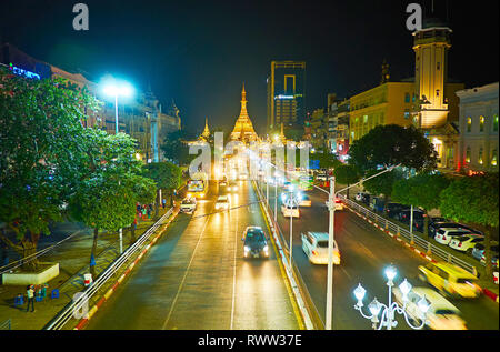 Evening traffic along Sule road, located in Downtown, the giant golden Sule Pagoda is seen on background,  Yangon, Myanmar. - Stock Photo