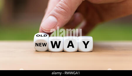 Hand is turning a dice and changes the expression 'old way' to 'new way' - Stock Photo