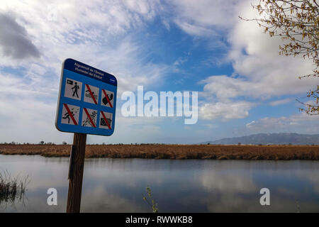 Sign and Wide open spaces, lakes and reed-beds, The Ebro Delta nature reserve, near Amposta, Catalunya, Spain - Stock Photo