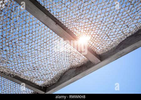 Sun canopy under blue sky with shining sun - Stock Photo