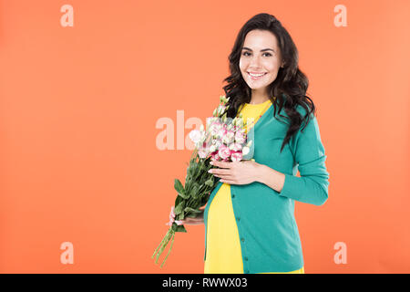 Charming brunette pregnant woman holding flower bouquet isolated on orange - Stock Photo