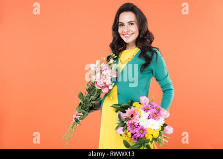 Blissful pregnant young woman holding flower bouquets isolated on orange - Stock Photo