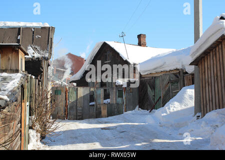 old wooden village house with outbuildings in the winter in Russia - Stock Photo