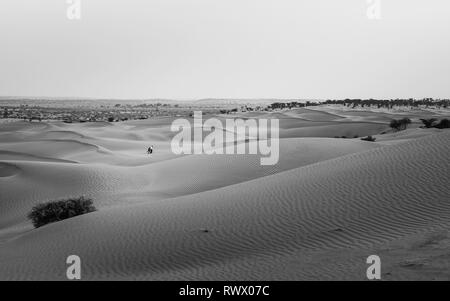 View across the sand dunes with a couple walking across the sand at dusk in summer near Jaisalmer, Rajasthan, India. - Stock Photo