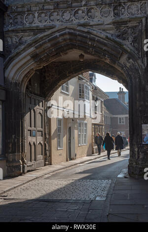 Salisbury, Wiltshire, England, UK. March 2019. Visitors passing through the North Gate of the city towards Cathedral Close from the High Street - Stock Photo