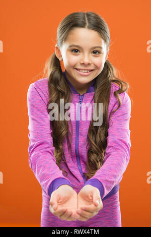 Look here. Kid happy smiling face show something in both hands copy space. Girl demonstrate product. Advertisement and commercial concept. Promoting product for kids. Launching product for children. - Stock Photo