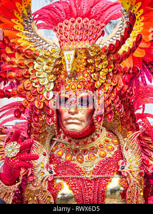 Venice, Italy - March 1, 2019  Portrait - Detail of a person wearing an elaborated motive red costume during Carnival of Venice - Stock Photo