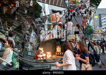The glass shopping entrance to a mall in Harajuku, Tokyo, reflects people walking past in the street outside the building. Japan - Stock Photo