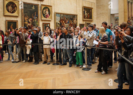 Paris, France - September 12, 2018: A big crowd of tourist lines up at the barrier in front of the Mona Lisa in the Louvre. - Stock Photo