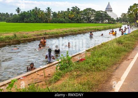 Tissamaharama, Sri Lanka - December 27, 2018: Local people bathing in river. Tissamaharama, Sri Lanka. - Stock Photo