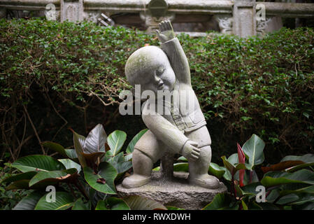 Fo Guang Shan - Largest Buddhist Monastery in Taiwan-A cute small stone buddha statue in the gardens of the temple in exercise pose. Kaohsiung, 2018 Stock Photo