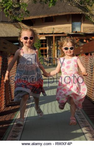 Two kids running hand in hand towards the camera. Wearing summer dress and sunglasses. Sunset time, holiday emotion. - Stock Photo