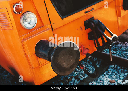 Abstract of a small orange locomotive, focus on lights and metal parts. - Stock Photo