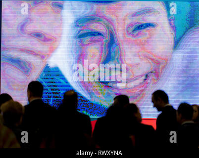 Berlin, Germany. 07th Mar, 2019. Visitors pass by a video screen at the China stand. Credit: Soeren Stache/dpa/Alamy Live News - Stock Photo