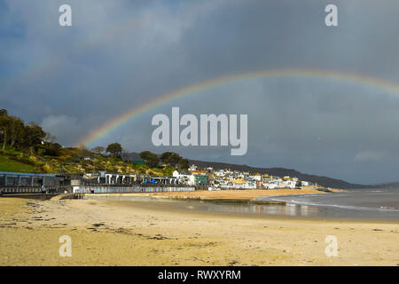 Lyme Regis, Dorset, UK.  7th March 2019. UK Weather.  A rainbow arches over the seaside town of Lyme Regis in Dorset on an afternoon of sunshine and showers.   Picture Credit: Graham Hunt/Alamy Live News - Stock Photo