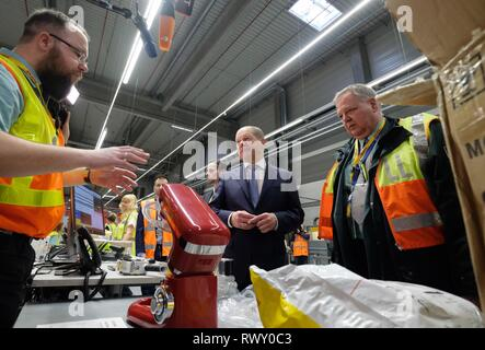 Schkeuditz, Germany. 07th Mar, 2019. Olaf Scholz (SPD, M), Federal Minister of Finance, talks to customs officials during the visit of the logistics company DHL to Leipzig-Halle Airport. He wanted to find out on the spot how customs at the international logistics hub are preparing for the clearance of cross-border goods traffic after the UK leaves the EU. Credit: Sebastian Willnow/dpa-Zentralbild/ZB/dpa/Alamy Live News - Stock Photo