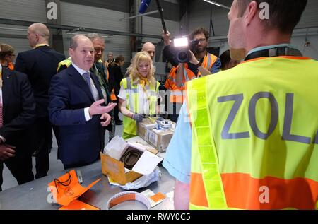 Schkeuditz, Germany. 07th Mar, 2019. Olaf Scholz (SPD, l), Federal Minister of Finance, talks to customs officials during the visit of the logistics company DHL to Leipzig-Halle Airport. He wanted to find out on the spot how customs at the international logistics hub are preparing for the clearance of cross-border goods traffic after the UK leaves the EU. Credit: Sebastian Willnow/dpa-Zentralbild/ZB/dpa/Alamy Live News - Stock Photo