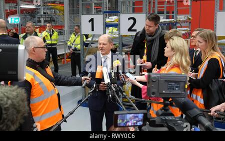 Schkeuditz, Germany. 07th Mar, 2019. Olaf Scholz (SPD, M), Federal Minister of Finance, talks to media representatives during the visit of the logistics company DHL to Leipzig-Halle Airport. He wanted to find out on the spot how customs at the international logistics hub are preparing for the clearance of cross-border goods traffic after the UK leaves the EU. Credit: Sebastian Willnow/dpa-Zentralbild/ZB/dpa/Alamy Live News - Stock Photo