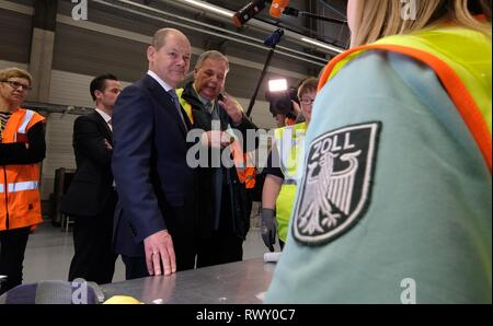 Schkeuditz, Germany. 07th Mar, 2019. Olaf Scholz (SPD, l), Federal Minister of Finance, talks to a customs officer during the visit of the logistics company DHL to Leipzig-Halle Airport. He wanted to find out on the spot how customs at the international logistics hub are preparing for the clearance of cross-border goods traffic after the UK leaves the EU. Credit: Sebastian Willnow/dpa-Zentralbild/ZB/dpa/Alamy Live News - Stock Photo