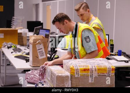 Schkeuditz, Germany. 07th Mar, 2019. Customs officers inspect shipments at the location of the logistics provider DHL at Leipzig-Halle Airport. Federal Finance Minister Scholz (SPD) informed himself on the spot how the customs authorities at the international logistics hub are preparing for the clearance of cross-border goods traffic following the departure of Great Britain from the EU. Credit: Sebastian Willnow/dpa-Zentralbild/ZB/dpa/Alamy Live News - Stock Photo