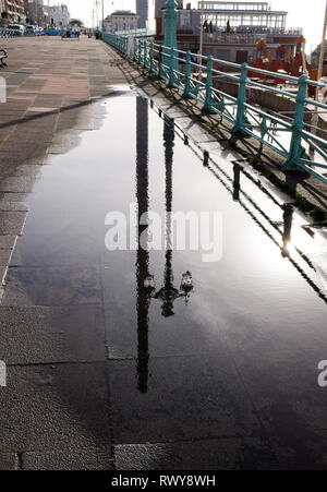 Brighton, UK. 8th Mar, 2019. Brighton seafront is reflected in a puddle on a beautiful sunny morning after heavy showers the previous day Credit: Simon Dack/Alamy Live News - Stock Photo