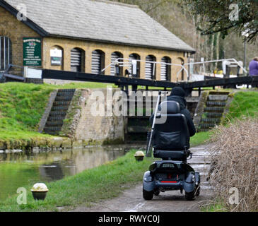 Mobility Scooter travelling along the towpath at the Grand Union Canal, Aston Clinton, Buckinghamshire / Hertfordshire Border, England, UK Credit: Susie Kearley/Alamy Live News - 8th Mar 2019. - Stock Photo