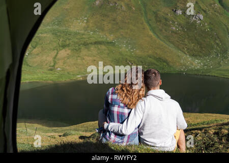 view from inside the tent of a girl and boy in love. swiss alps and a lake as background - Stock Photo