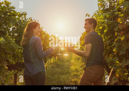 woman with denim shirt and man with t-shirt drinking red wine during sunset. grapevine in Ticino. - Stock Photo