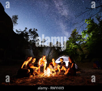Happy Friends hikers having a rest together around campfire beside camp and illuminated tourist tent at night. On background beautiful night starry sky full of stars and Milky way, mountain rocks. - Stock Photo