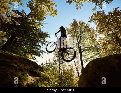 Young male biker jumping on trial bicycle between two big boulders, professional rider making acrobatic trick in the forest on sunny day. Concept of extreme sport active lifestyle - Stock Photo