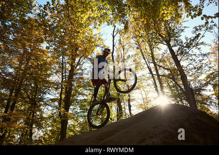 Silhouette of professional cyclist standing on back wheel on trial bicycle, sportsman rider balancing on the edge of big boulder in the forest. Concept of extreme sport active lifestyle - Stock Photo
