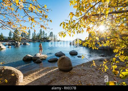 Young woman in bikini standing on a round stone in the water, bay at lake Lake Tahoe, Sand Harbor State Park, shore, California - Stock Photo