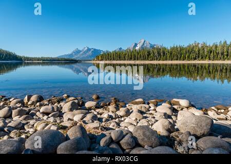 Mountains reflected in the lake, Colter Bay Bay, Jackson Lake, Teton Range Mountain Range, Grand Teton National Park, Wyoming - Stock Photo