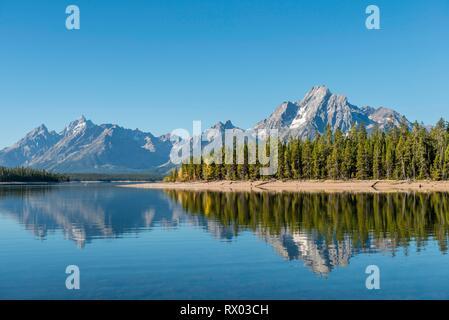 Mountains reflected in a lake, Colter Bay Bay, Jackson Lake, Teton Range Mountain Range, Grand Teton National Park, Wyoming, USA - Stock Photo