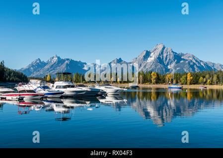 Mountains reflected in the lake, Jackson Lake, sailing boats in a bay, Colter Bay, Teton Range mountain range - Stock Photo