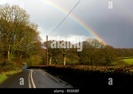 rainbow,rural,road,double,white,no,over,taking,lines,after,rain,storm,slippery,conditions,dangerous,country,village,speed,slippery,slide,crash,acciden - Stock Photo