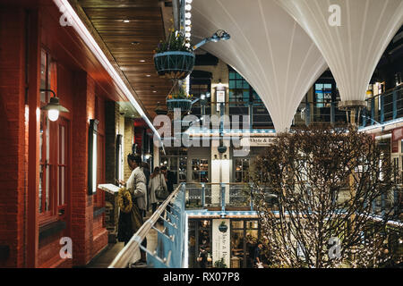 London, UK - March 6, 2019: People inside Kingly Court, a three-storey alfresco food and dining courtyard in the heart of London's West End. - Stock Photo