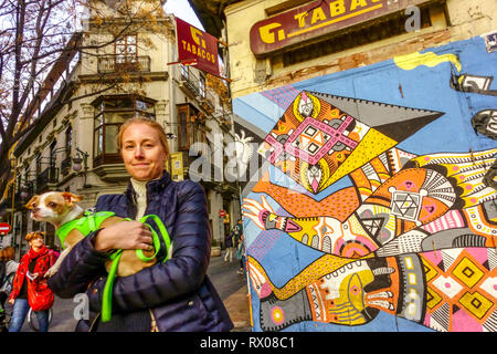 Street view, a woman with a dog in her arms, Valencia, Old Town, El Carmen district - Stock Photo