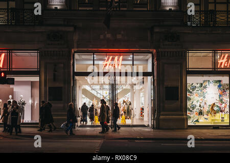London, UK - March 6, 2019: People walking in front of H&M store on Regent Street, London, in the evening. Regent Street is one of the most famous sho
