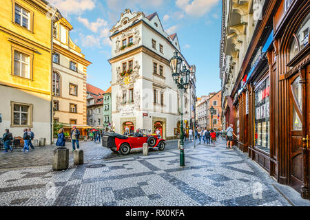 Tourists sightsee, shop and enjoy the cafes as they pass by a vintage red automobile in a picturesque section of Old Town Prague, Czech Republic. - Stock Photo