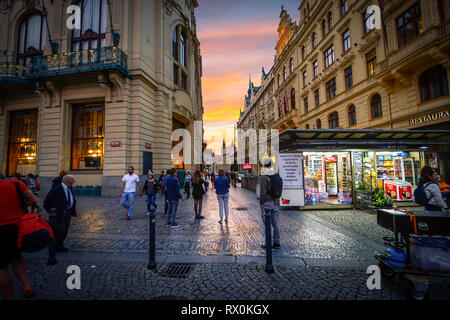 Tourists and local Czech enjoy a brilliant sunset outside a small shop in Republic square with the Tyn Towers of Old Town in view at Prague, Czechia - Stock Photo