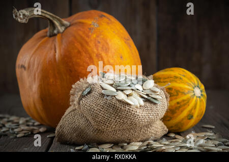 Canvas bag of pumpkins seeds and two pumpkins on wooden table. - Stock Photo